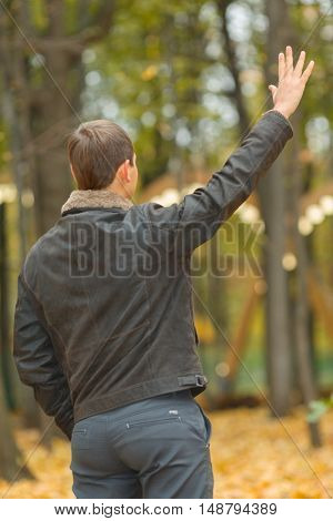 young man in black jacket in autumn park someone waves hand, seen from behind, focus on hand