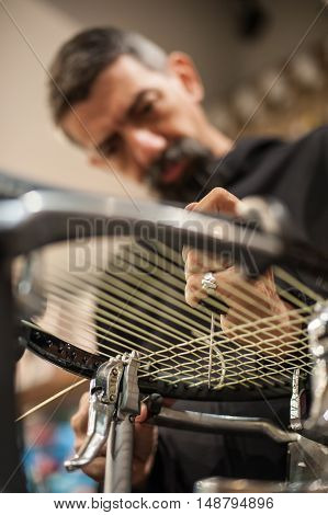 Tennis Stringer Holding Awl And Doing Racket Stringing