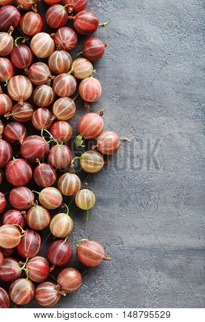 Gooseberries fruit on a grey table, close up