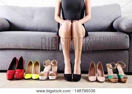 Woman Choosing Shoes On High Heels On Grey Sofa