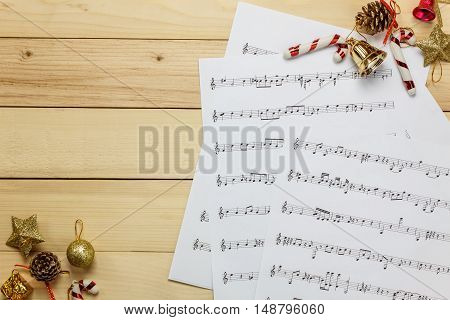Create music sheet note paper by myself.Top view music sheet note paper and Christmas decoration on wood background.