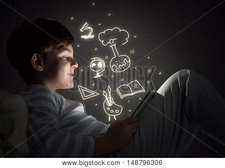 Teenage boy in pajamas lying in bed using tablet pc