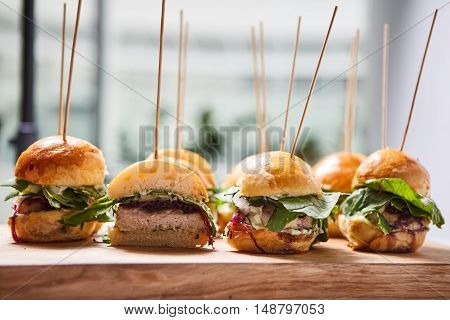 Macro close up of multiple appetizing mini chicken burgers on wooden surface.