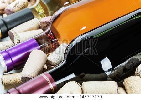 different varieties Wine and corks on a light background. Focus on the middle of the bottle