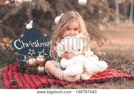 Smiling baby girl 4-5 year old holding teddy bear toy sitting with christmas decorations outdoors. Looking at camera.