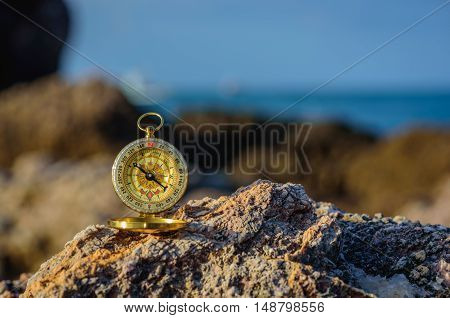 Analogical compass abandoned on the rocks with blurred sea background.