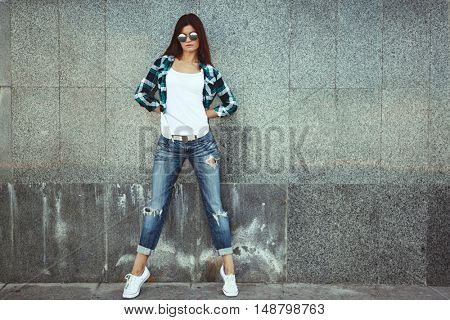 Hipster girl wearing white t-shirt, fashion sunglasses and jeans posing against wall, swag street style