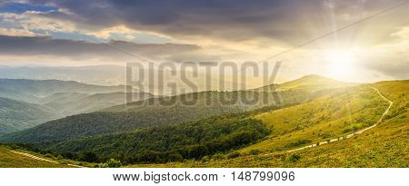 panoramic summer landscape with road through hillside meadow in mountains in evening light