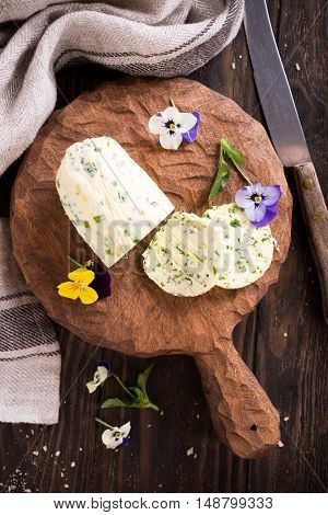 Herb butter with edible flowers on wooden cutting board, healthy food. Top view.