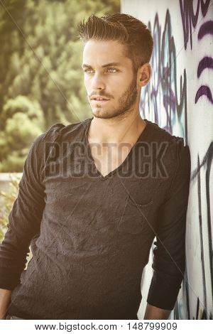 Attractive young man leaning against colorful graffiti wall, looking at camera