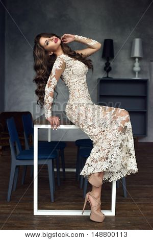 Gorgeous stunning glamorous girl in white lace luxury evening dress sitting on table and posing in lounge stylish interior. Fashionable vogue style portrait of beautfiul brunette with long curly hair