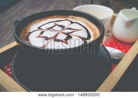 hot coffee with foam milk art. Coffee mocha on the wood desk.(selective focus vintage effect)
