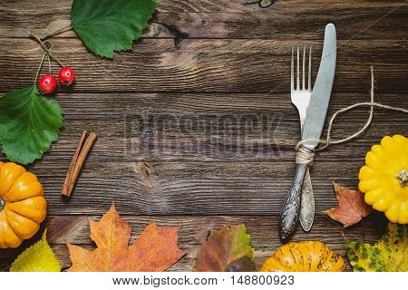 Autumn table setting. Fallen leaves, small pumpkins, empty plate, fork and knife on wooden table. Top view