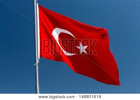 Turkish flag fluttering on a wind with deep blue sky on background
