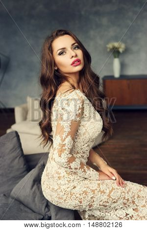 Young stylish sexy girl in white lace evening dress sitting on gray couch in simple lounge interior.
