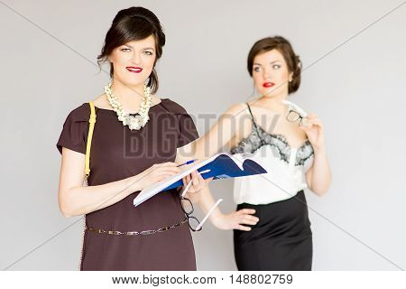 two girl in a business suit with glasses on a gray background