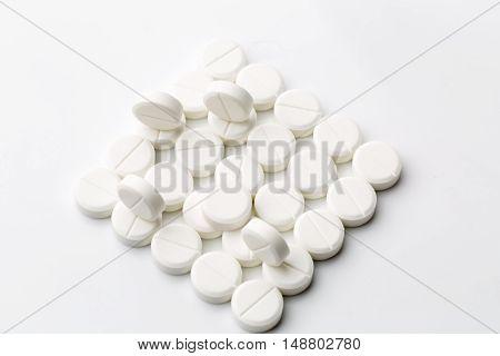 Heap of round white pills on white background