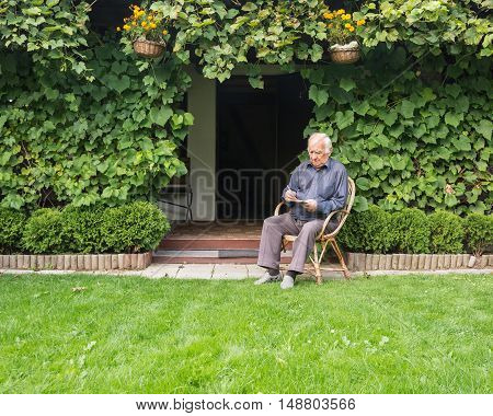 Grandfather on chair reading a book in garden