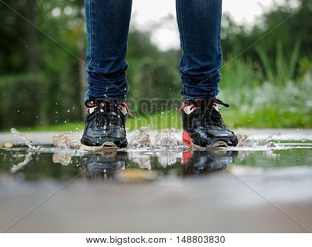 Human Legs in jeans and sneakers in a puddle. Splashes of water. Run jump in puddles