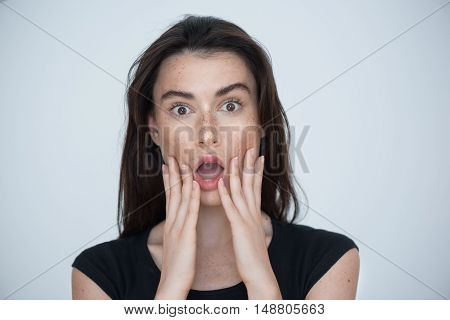 portrait of a shocked attractive woman looking into camera isolated on light grey background with copyspace