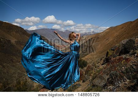 Fashion Photo Of Beautiful Woman In Long Blue Dress On The Mountain Background