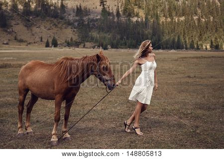 Young Beautiful Woman In White Dress Walking With Horse
