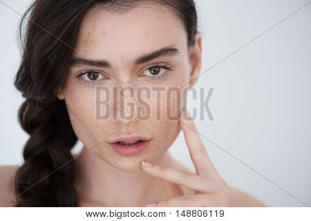 skin and hair care concept, close up of a freckled modern woman