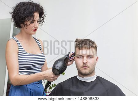 The young man at the hairdresser salon hairstyle