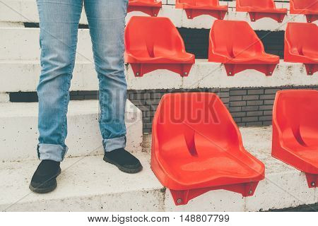 Team supporter standing on empty stadium with red seats