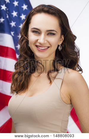 Portrait of a happy young woman on a background of the American flag