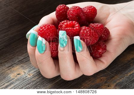 The female hand with beautiful manicure holds a handful of ripe berries of raspberry against the background of a wooden table
