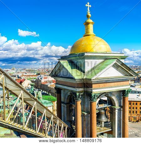 SAINT PETERSBURG RUSSIA - APRIL 25 2015: The tourists on the covered staircase climb to the rooftop of the St Isaac's Cathedral overlooking beautiful bell towers and city roofs on April 25 in Saint Petersburg.