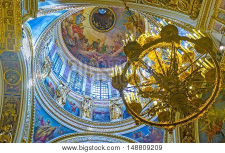 SAINT PETERSBURG RUSSIA - APRIL 25 2015: The amazing great dome of St Isaac's Cathedral decorated with frescoes golden patterns and sculptures on April 25 in Saint Petersburg.