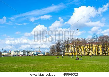SAINT PETERSBURG RUSSIA - APRIL 25 2015: People relax and enjoy the views on the lawn of Senate Square on April 25 in Saint Petersburg.