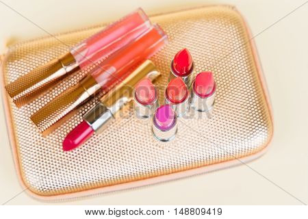 Collection of colorful lipsticks on golden woman pursue