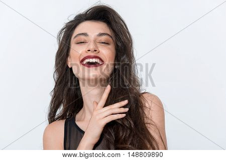 young smiling girl standing on white background with copy space