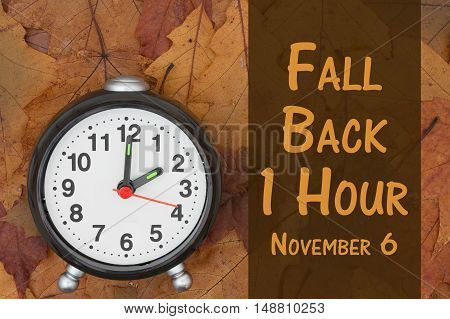 Daylight Savings Time message Some fall leaves and retro alarm clock with text Fall Back 1 Hour November 6