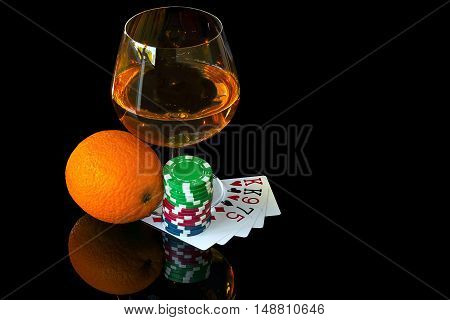 Cards with colorful chips to play poker and snifter of brandy