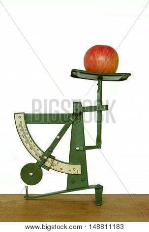 old fashioned letter scale with apple on white background