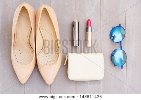 Nude colored high heels still life with wallet, sunglasses and red lipstick, top view