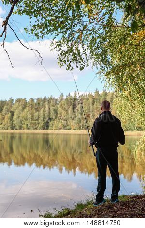 Silhouette Fisherman on the autumn lake. Fisherman in his hand holding spinning.