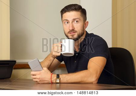 business man with cup and cell phone in hand sitting at the table