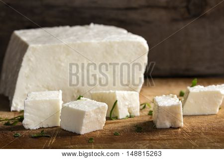 Feta cheese cubes and herbs on a wooden rustic background