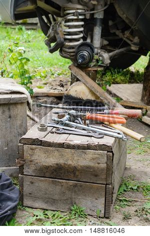 car repair in the field, tools lie on an old wooden box.