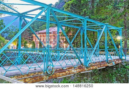 The blue bridge over Borjomula river with brightly illuminated building on the background Borjomi Georgia.