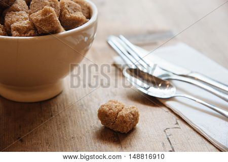 Bowl with brown sugar and small sugar piece on the wooden table with silverwear
