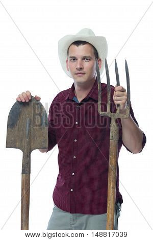 A farmer in a hat with a shovel and pitchfork in hand