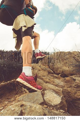 Female hiker walking through the rocky land. Focus on the foot