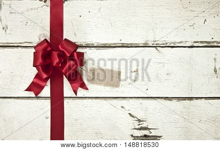 Red satin Christmas bow and ribbon with gift tag on old painted white wood background
