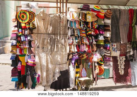 Street showcase with colorful crocheted and knitted hats shawls scarfs. Arbat street in Moscow Russia.